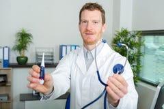 Hübscher männlicher Doktor, der Thermometer hält lizenzfreie stockfotos