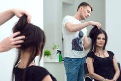 Hübscher männlicher Friseur stellt das Haar her, das für seinen Kunden am Schönheitssalon anredet Lizenzfreies Stockfoto
