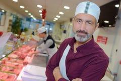 Hübscher männlicher Metzger, der mit Fleisch im Speicher arbeitet lizenzfreie stockfotos