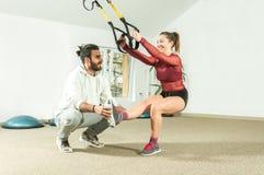 Hübscher männlicher persönlicher Trainer mit einem Bart, der jungem schönem Mädchen für Aerobic-Übung in der Turnhalle, selektive Stockfotos