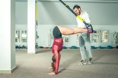 Hübscher männlicher persönlicher Trainer mit einem Bart, der jungem schönem Mädchen für Aerobic-Übung in der Turnhalle, selektive Stockfoto