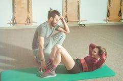 Hübscher männlicher persönlicher Trainer mit einem Bart, der jungem schönem Mädchen für Aerobic-Übung in der Turnhalle, selektive Lizenzfreie Stockfotos