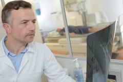 Hübscher männlicher Radiologe, der Röntgenstrahl hält stockbild