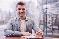 Hübscher männlicher Student, der mit Aufgabe kopiert lizenzfreie stockfotografie