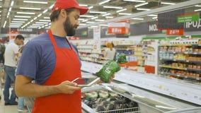 Hübscher männlicher Verkaufsberater in der roten Uniform Produkte mit digitaler Tablette überprüfend stock video