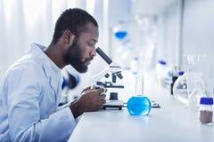 Hübscher männlicher Wissenschaftler, der das Mikroskop untersucht lizenzfreie stockfotografie