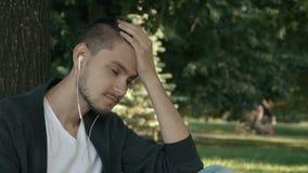 Hübscher müder junger Mann, der unter einem Baum sitzt stock video