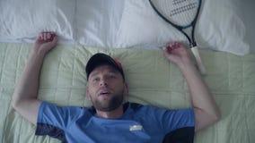 Hübscher müder Tennisspieler in der Sportausrüstung liegt auf dem Bett mit einem Tennisschläger im Hotel Aktiver Lebensstil stock video footage