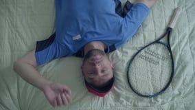 Hübscher müder Tennisspieler in der Sportausrüstung liegt auf dem Bett mit einem Tennisschläger im Hotel Aktiver Lebensstil stock footage