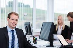 Hübscher Manager, der an seinem Schreibtisch sitzt Stockbild