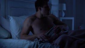 Hübscher Mann, der im Bett, enttäuschende Textnachricht auf Smartphone aufhebend liegt stock video footage