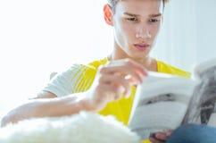 Hübscher Mann fokussiert, ein Buch lesend stockfotografie