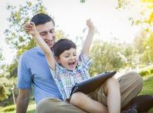 Hübscher Mischrasse-Vater und Sohn, die auf Computer-Tablet spielt Stockfoto
