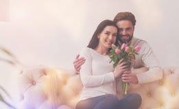 Hübscher mitfühlender Ehemann, der einen Blumenstrauß darstellt Lizenzfreie Stockfotografie