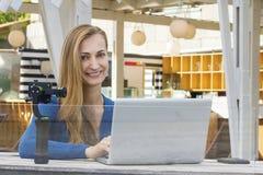 Hübscher Mode Blogger, der draußen Strombericht mit mohito macht Lizenzfreie Stockfotografie
