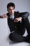 Hübscher Modemann, der auf dem Boden sitzt Stockfotografie
