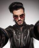 Hübscher Modemann, der die Kamera mit seinen Händen hält Stockbild