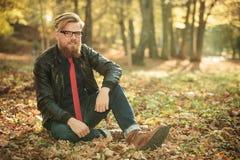 Hübscher Modemann, der im Park, entspannend sitzt Lizenzfreies Stockbild