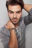 Hübscher Modemann, der seine Hand auf seinem Hals hält Stockbild