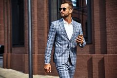 Hübscher moderner Geschäftsmann, der auf Straßenhintergrund aufwirft stockfoto