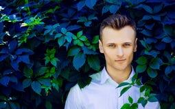 Hübscher moderner junger Mann, der in den Blättern von einem wilden steht Stockbilder