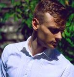Hübscher moderner junger Mann, der in den Blättern von einem wilden steht Lizenzfreie Stockfotografie