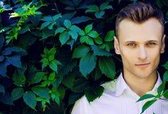 Hübscher moderner junger Mann, der in den Blättern von einem wilden steht Stockfotos