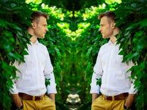 Hübscher moderner junger Mann, der in den Blättern von einem wilden steht Lizenzfreie Stockfotos
