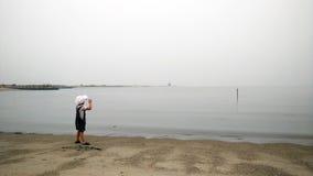 Hübscher moderner kleiner Junge, der auf sandigen Strand geht Stockfoto