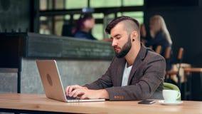 Hübscher modischer männlicher Geschäftsmann, der online unter Verwendung des Computer-PC sitzt auf Tabelle am Café plaudert stock video