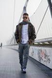 Hübscher modischer Mann, der auf eine Brücke im Winter geht Lizenzfreie Stockfotografie