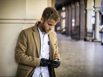 Hübscher modischer Mann, der Handy verwendet, um Text zu schreiben Stockbild