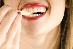 Hübscher Mund, der Pommes-Frites isst Lizenzfreie Stockbilder