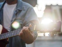 Hübscher Musiker, der Akustikgitarre auf Unschärfehintergrund spielt MU Stockfotos