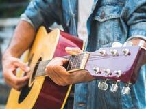 Hübscher Musiker, der Akustikgitarre auf Unschärfehintergrund spielt wo Stockfotografie