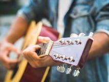 Hübscher Musiker, der Akustikgitarre auf Unschärfehintergrund spielt wo Stockbild