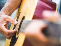 Hübscher Musiker, der Akustikgitarre auf Unschärfehintergrund spielt wo Lizenzfreie Stockfotos