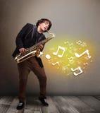 Hübscher Musiker, der auf Saxophon mit musikalischen Anmerkungen spielt Lizenzfreie Stockfotografie