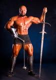 Hübscher muskulöser alter Krieger mit einer Klinge und einer Muskatblüte Stockbild