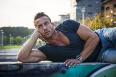 Hübscher muskulöser blonder Mann, der in der Stadt niederlegt Stockbild