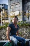Hübscher muskulöser blonder Mann, der in der Stadteinstellung sitzt Lizenzfreie Stockbilder