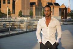Hübscher muskulöser blonder Mann, der in der Stadteinstellung steht Stockbild