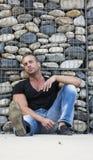 Hübscher muskulöser blonder Mann, der gegen Steinwand sitzt Stockfoto