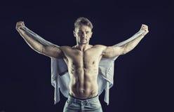 Hübscher muskulöser hemdloser junger Mann, der Hemd hält Stockbilder