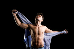 Hübscher muskulöser hemdloser junger Mann, der T-Shirt hält Lizenzfreie Stockfotografie