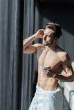 Hübscher, muskulöser, junger Mann, der seinen Morgenkaffee in einem h trinkt lizenzfreie stockfotos