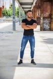 Hübscher muskulöser Mann, der in der Stadteinstellung steht Lizenzfreies Stockfoto