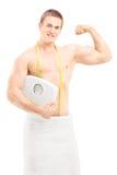 Hübscher muskulöser Mann im Tuch, das eine Gewichtsskala hält Stockfoto