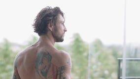 Hübscher muskulöser Mann mit Tätowierungen auf seinem bloßen Rückwärtsschritt heraus auf den offenen Balkon stock video footage