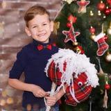 Hübscher netter Junge, der neues Jahr-Weihnachten allein nah an Weihnachtsbaum auf dem roten Kissen aufwirft in tragenden Jeans d lizenzfreies stockbild
